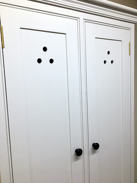 Freestanding larder cupboard with cutout door motifs