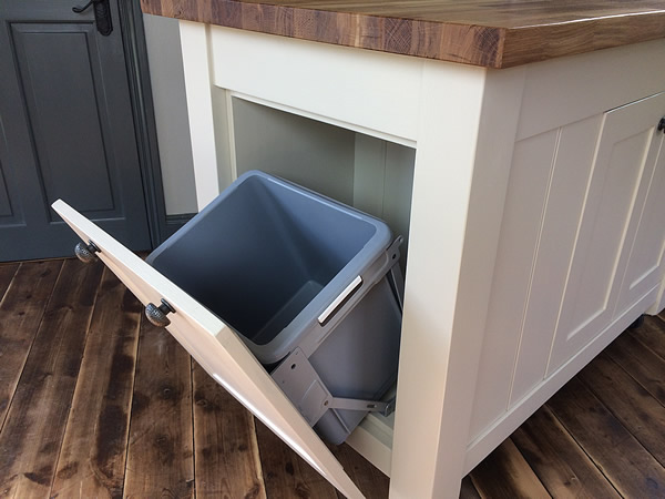 Freestanding kitchen island containing a fitted pull-out waste bin