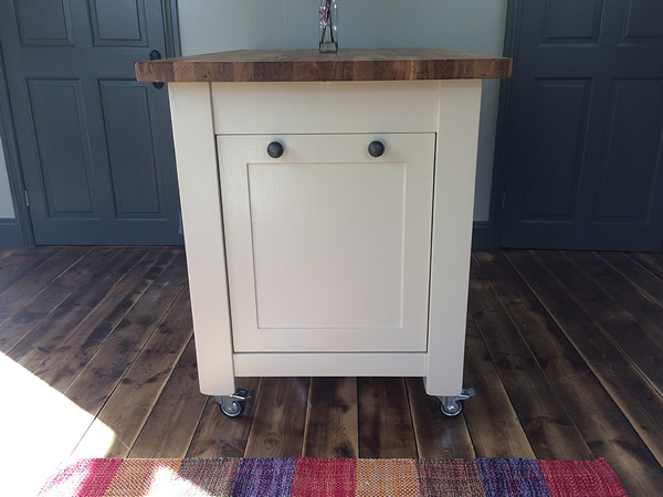 Freestanding kitchen island fitted with tilting waste bin