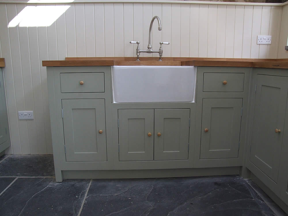 Painted Belfast sink unit adjoing extra corner units fitted with an oak worktop