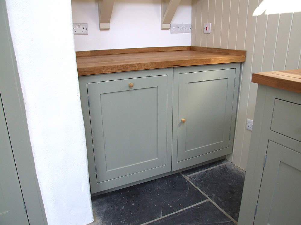 Integrate appliances concealed behind painted Shaker kitchen doors