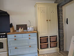 Painted Shaker kitchen with freestanding larder cupboard with wicker baskets